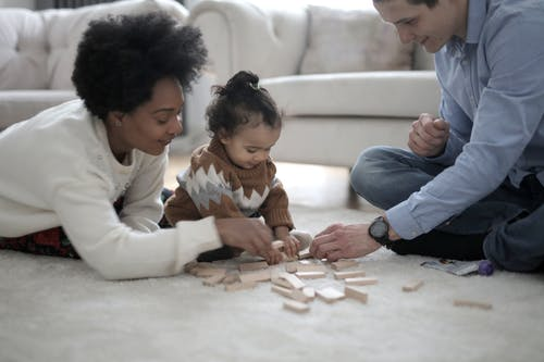Photo of Man and Woman Playing With Their Child