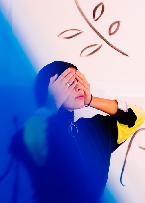 Young lady covering eyes with hands