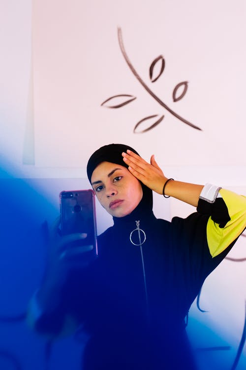 Concentrated young ethnic female wearing sportswear with tight hood covering head and taking selfie against white wall with abstract illustrations