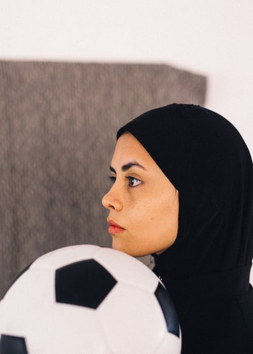 Woman in Black Hijab and Soccer Ball Near Her Face