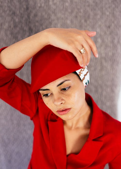 From above of young thoughtful female wearing retro hat and red jacket looking away in studio on gray background