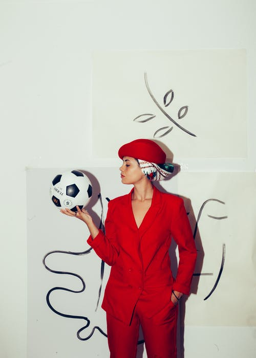 Woman in Red Blazer Holding White and Black Soccer Ball