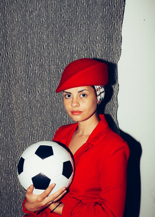 Woman in Red Coat While Holding Soccer Ball