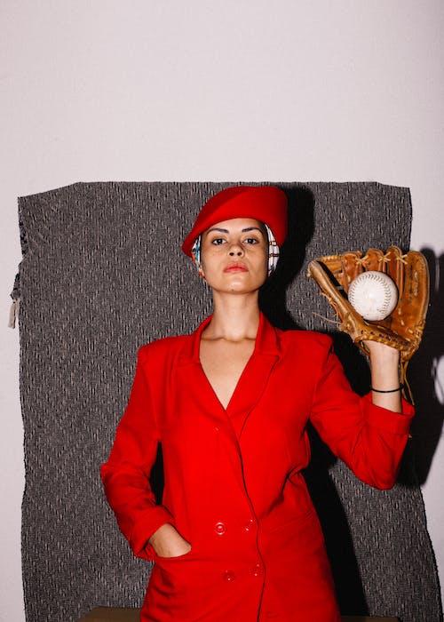 Woman in Red Coat Wearing Baseball Glove
