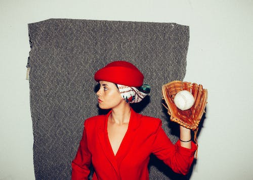 Woman in Red Coat Wearing Baseball Glove While Looking to Her Right