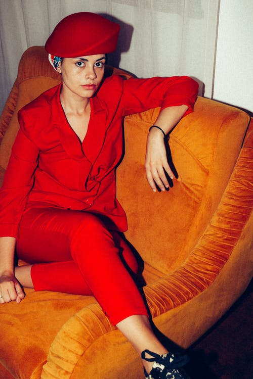 Woman in Red Blazer Sitting on Orange Sofa