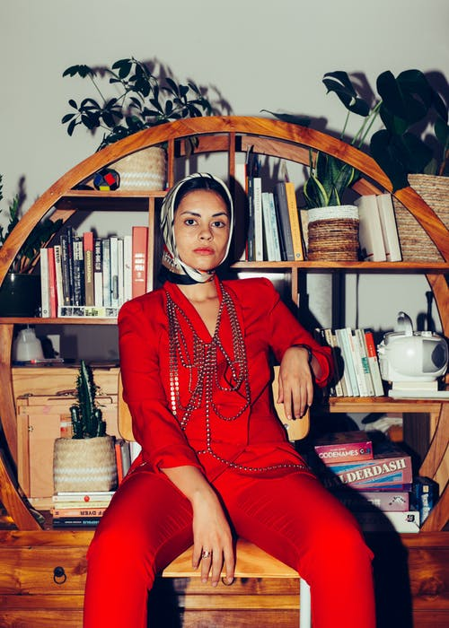 Calm female model wearing elegant suit and headscarf sitting on wooden chair on background of vintage bookcase and looking at camera