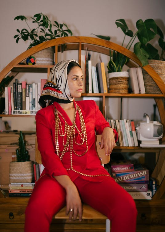 Trendy ethnic woman in fashionable clothes at home