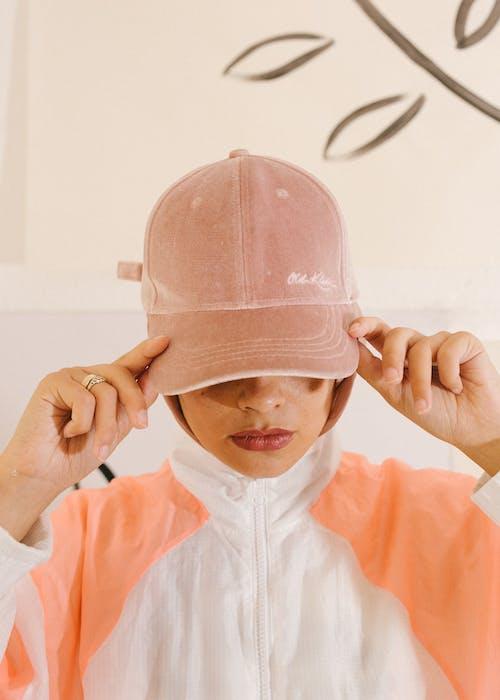 Serious female model in trendy cap in studio