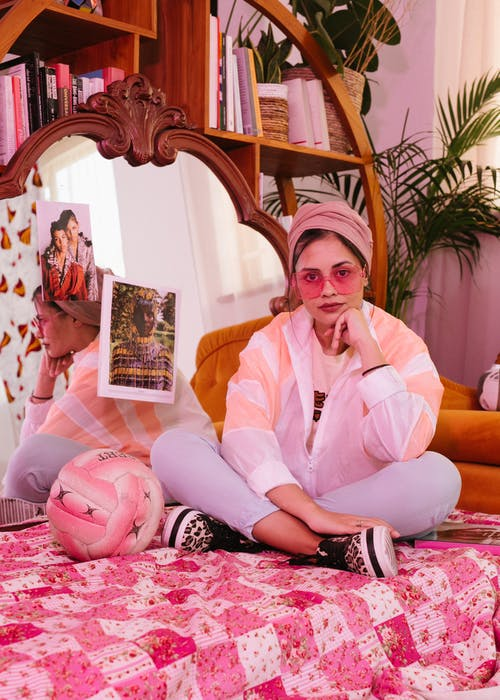 Photo of Woman Wearing Sunglasses While Sitting on Pink Bed