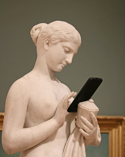 Classic female statue surfing internet on smartphone in museum