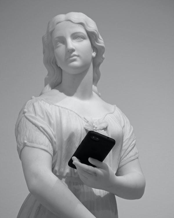 Vecchia Statua Di Giovane Donna Con Lo Smartphone Nel Museo