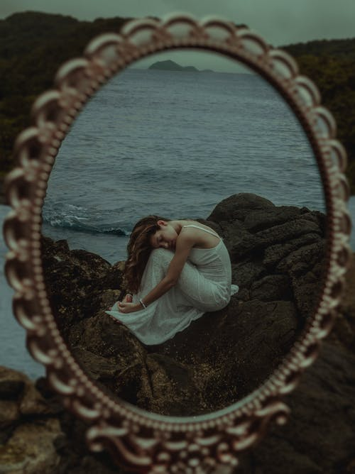 Reflection of Woman in White Dress Sitting on Brown Rock Near Body of Water