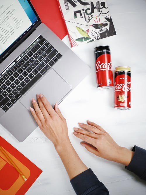 Person Using Macbook Pro Beside Coca Cola Cans