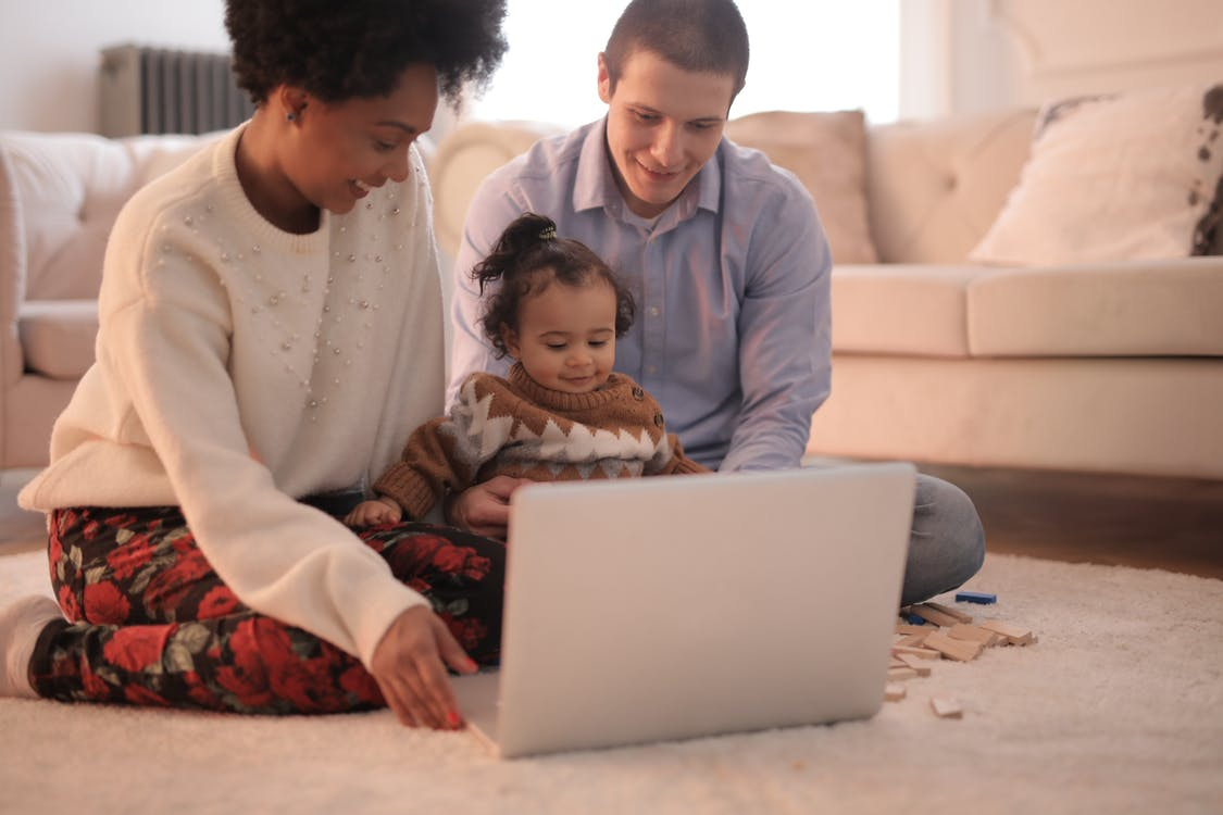 Photo of Family Sitting on Floor While Using Laptop