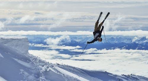 Unrecognizable skier performing upside down trick in snowy mountains