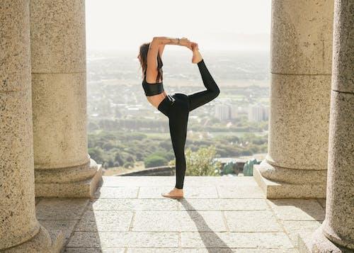 Woman in Black Leggings and Black Sports Bra Doing Yoga