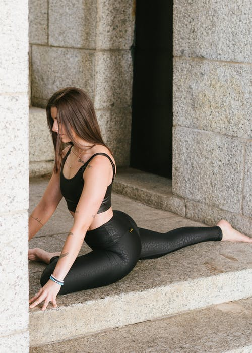 Woman in Black Tank Top and Black Leggings Practicing Yoga