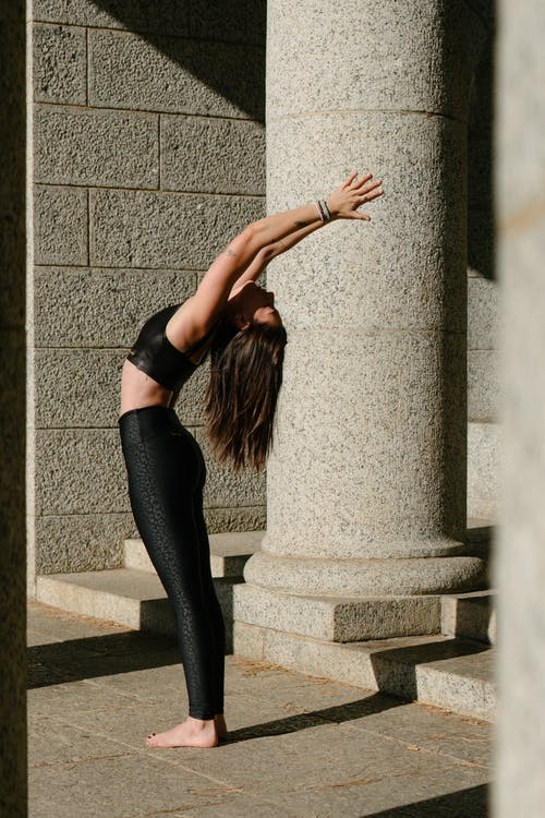 Photo of Woman in Black Sports Bra and Black Leggings Stretching