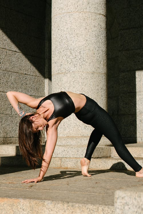 Woman in Black Tank Top and Black Leggings Bending Her Body