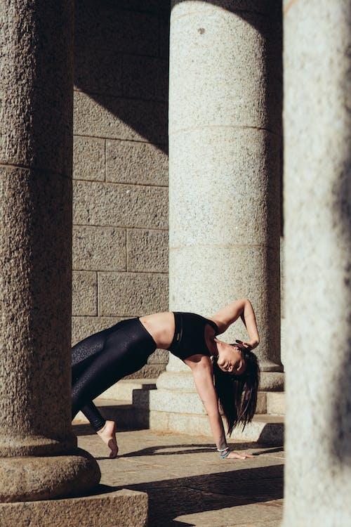 Woman in Black Sports Bra and Black Leggings Practicing Yoga