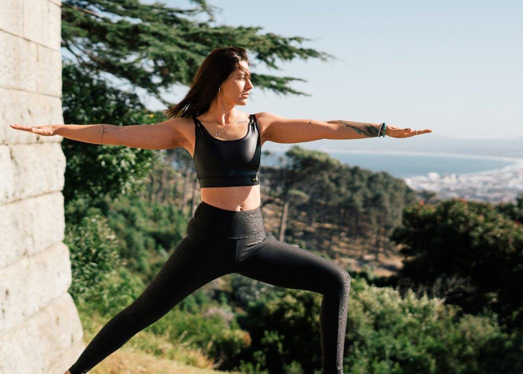 Woman in Black Sports Bra and Black Leggings Doing Yoga