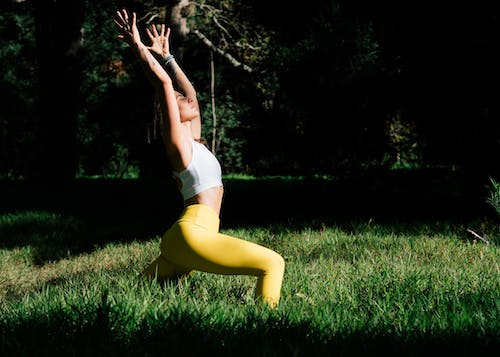 Woman in White Sports Bra and Yellow Leggings Practicing Yoga