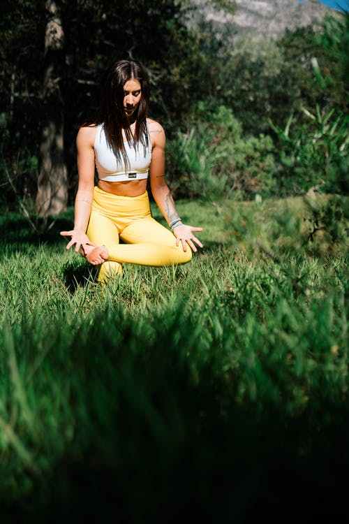 Photo of Woman Practicing Yoga on Grass Field