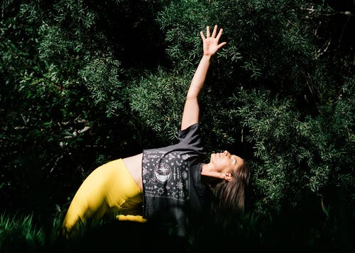 Photo of Woman Doing Yoga Near Dark Green Leaves