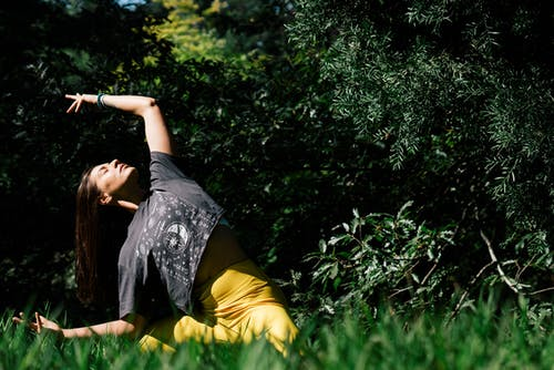Woman Doing Yoga Near Dark Green Leaves