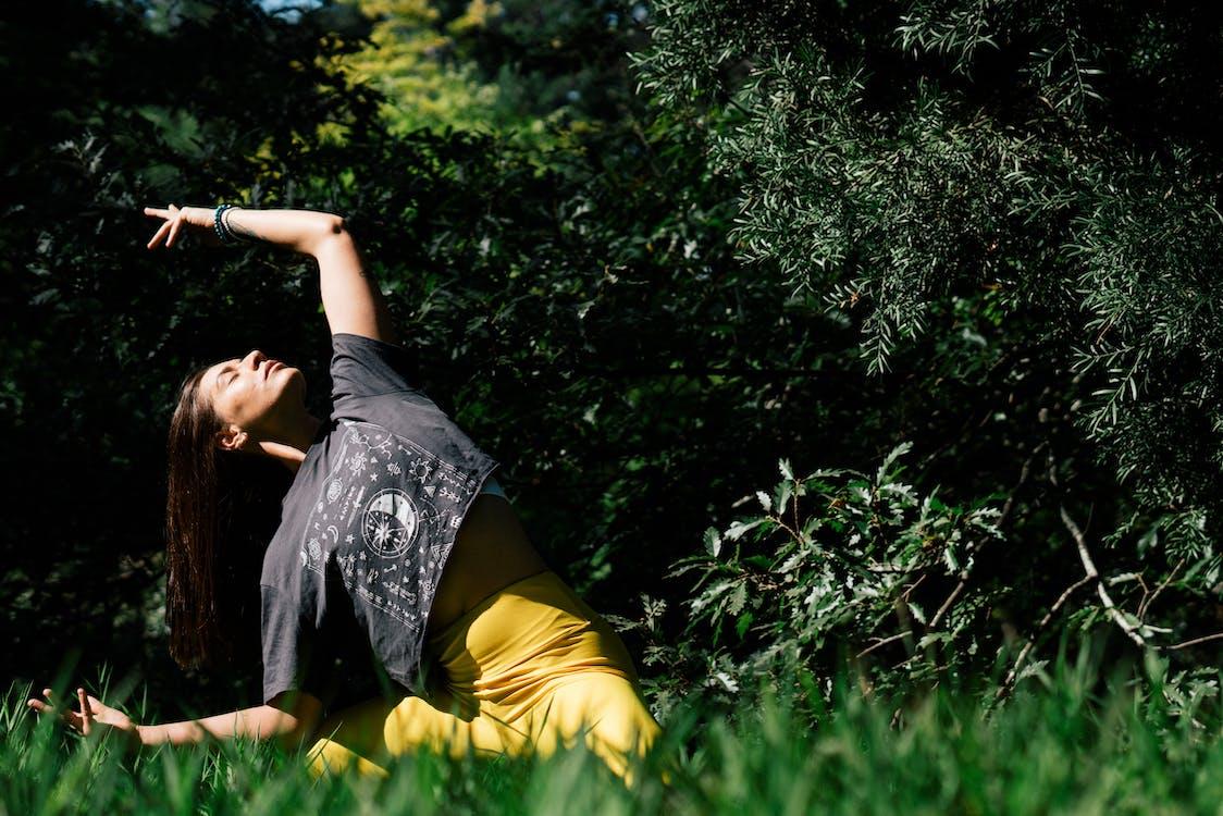Woman Doing Yoga Near Dark Green Leaves