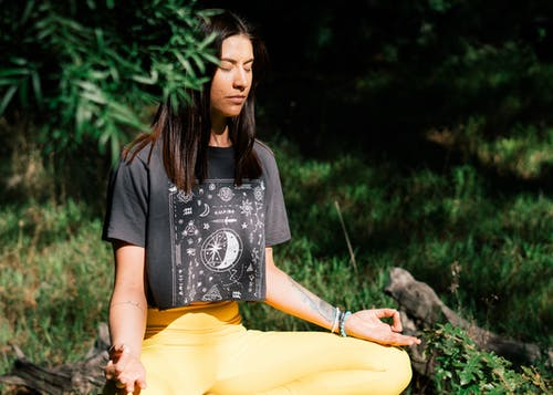 Woman in Black T-shirt and Yellow Pants Sitting on Rock