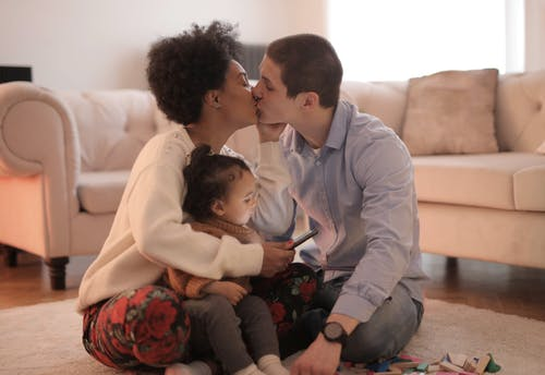 Man and Woman Kissing While Holding Baby