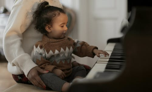 Girl in Brown Sweater Playing Piano