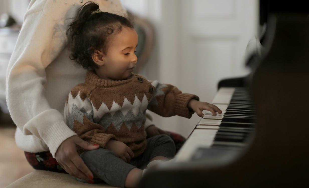 弹钢琴的棕色毛线衣的女孩