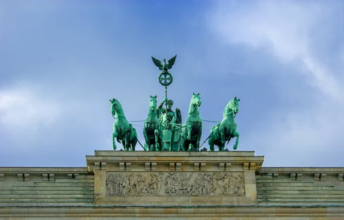 From below of historical heritage architectural monument of Germany representing ancient Greek Goddess of Peace in chariot with four horses holding metal cross with laurel wreath and eagle under sky