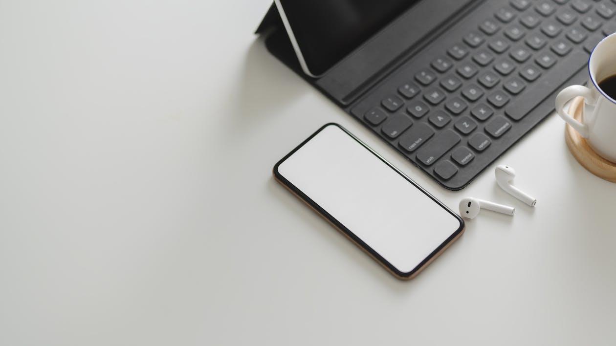 White Smartphone Near Black Keyboard