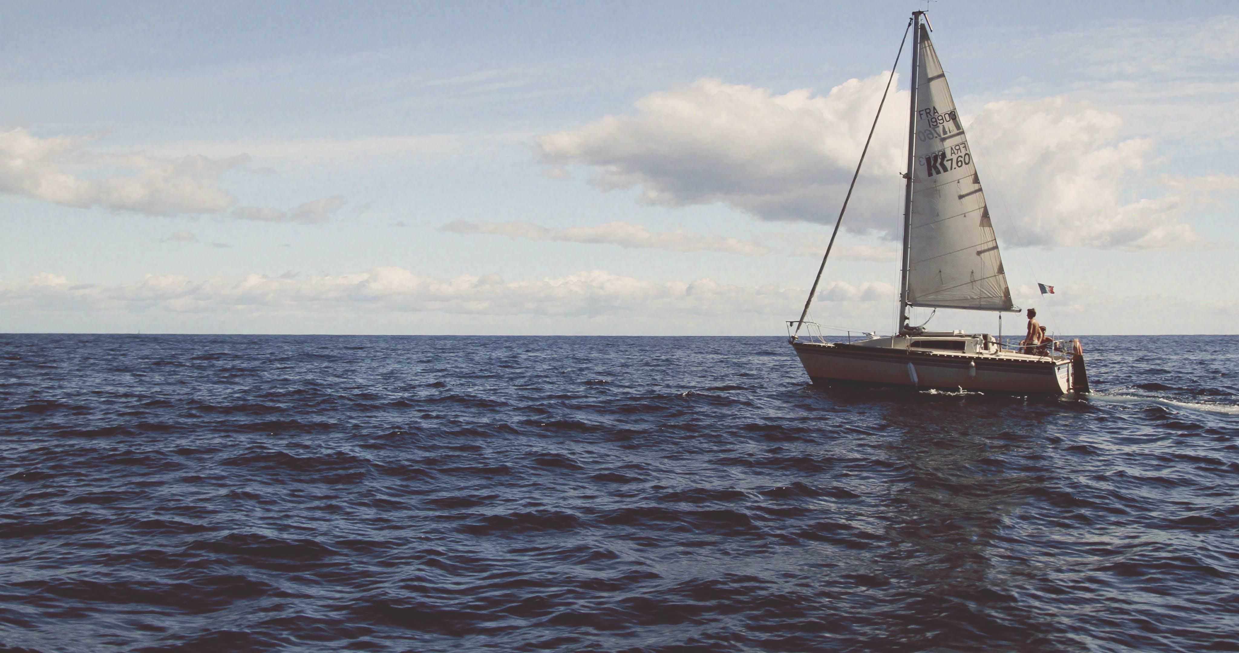 Boat in Body of Water Under Cloudy Sky