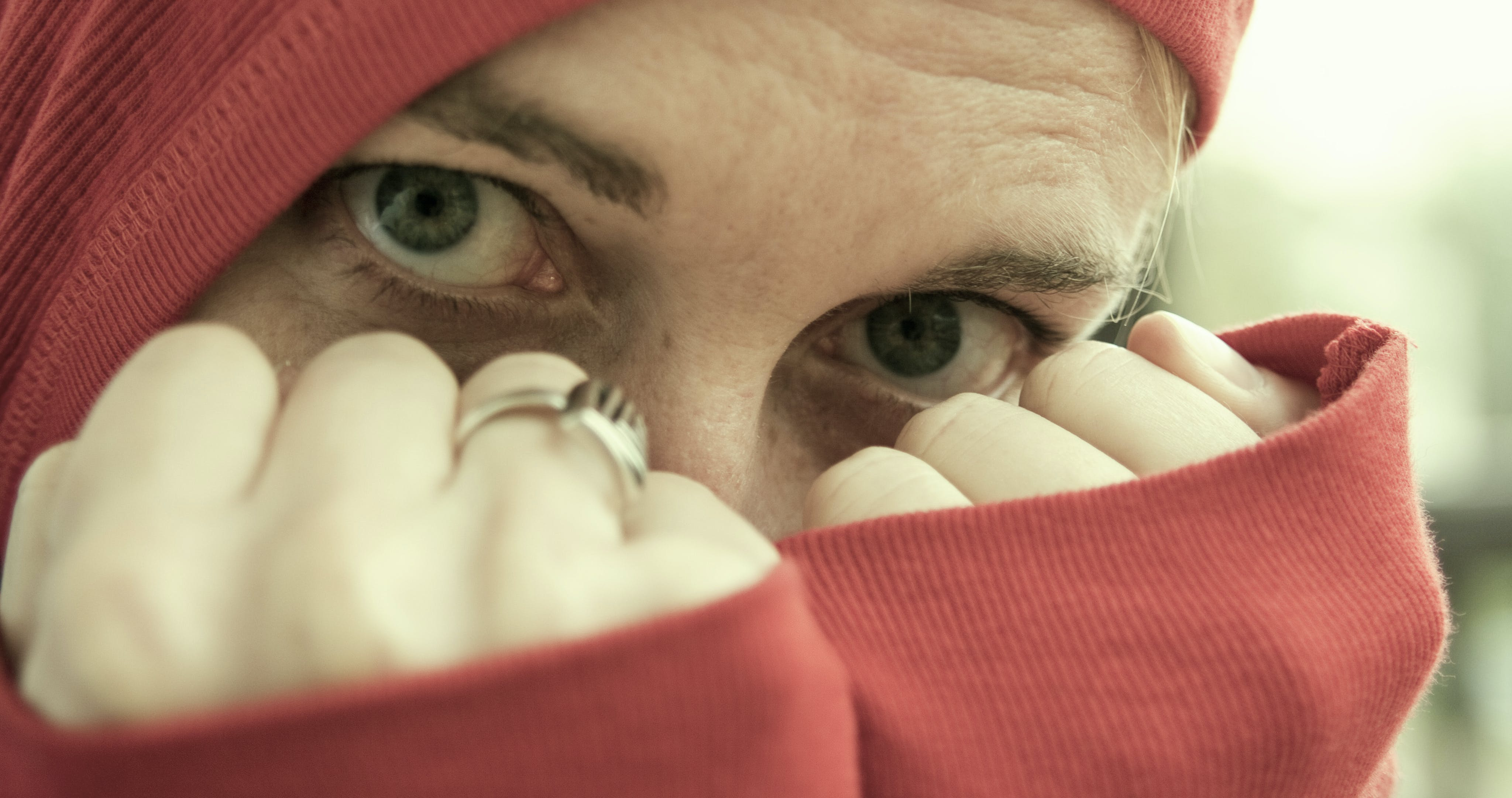 Person Wearing Red Hoodie and Gold-colored Ring Covering Face With Both Fists
