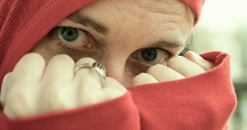 兩個拳頭都穿紅色連帽衫和金色的戒指覆蓋臉的人
