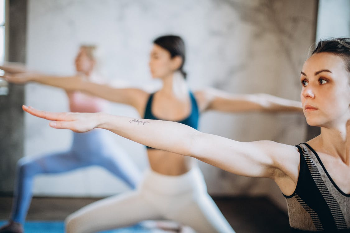 Woman in Blue Sports Bra and White Leggings Doing Yoga