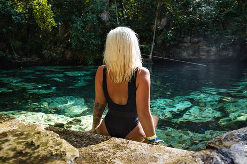 Woman in Black Bathing Suit Sitting on Rock Near Body of Water