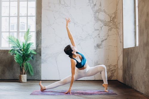 Woman in Blue Sports Bra and White Leggings Doing Yoga