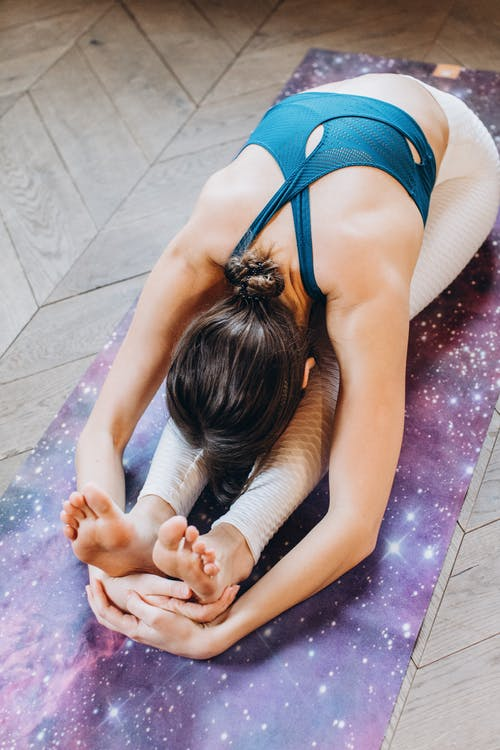 Woman in Blue Sports Bra and White Leggings Stretching