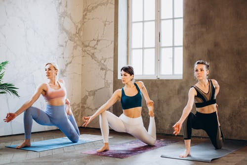 Women in Sports Bras and Leggings Doing Yoga