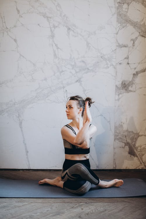 Woman in Black Sports Bra and Black Leggings Doing Yoga