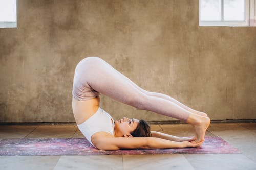 Woman in White Tank Top and Leggings Doing Yoga