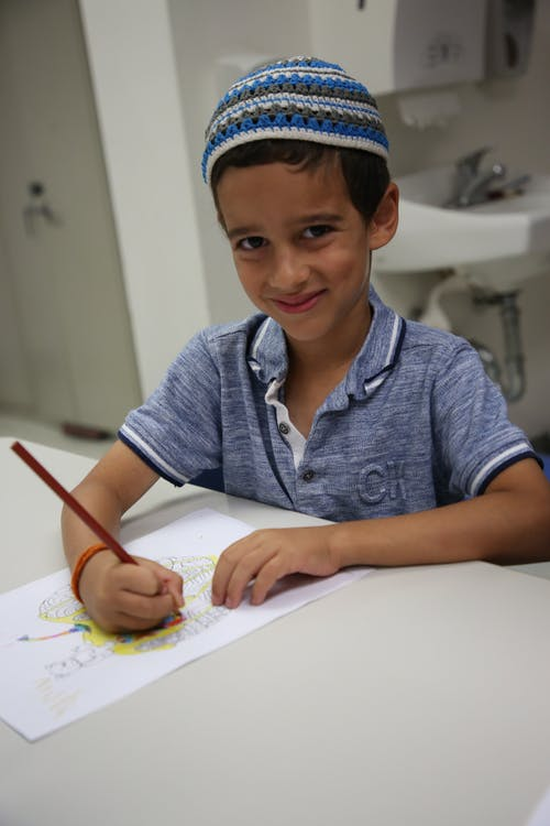 Boy Holding Pencil While Smiling
