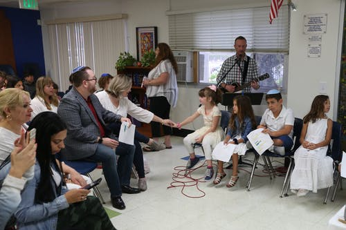 Children dressed in white sitting with sheets of paper near adult parents and musician playing guitar and singing into microphone during Bar mitzvah ceremony