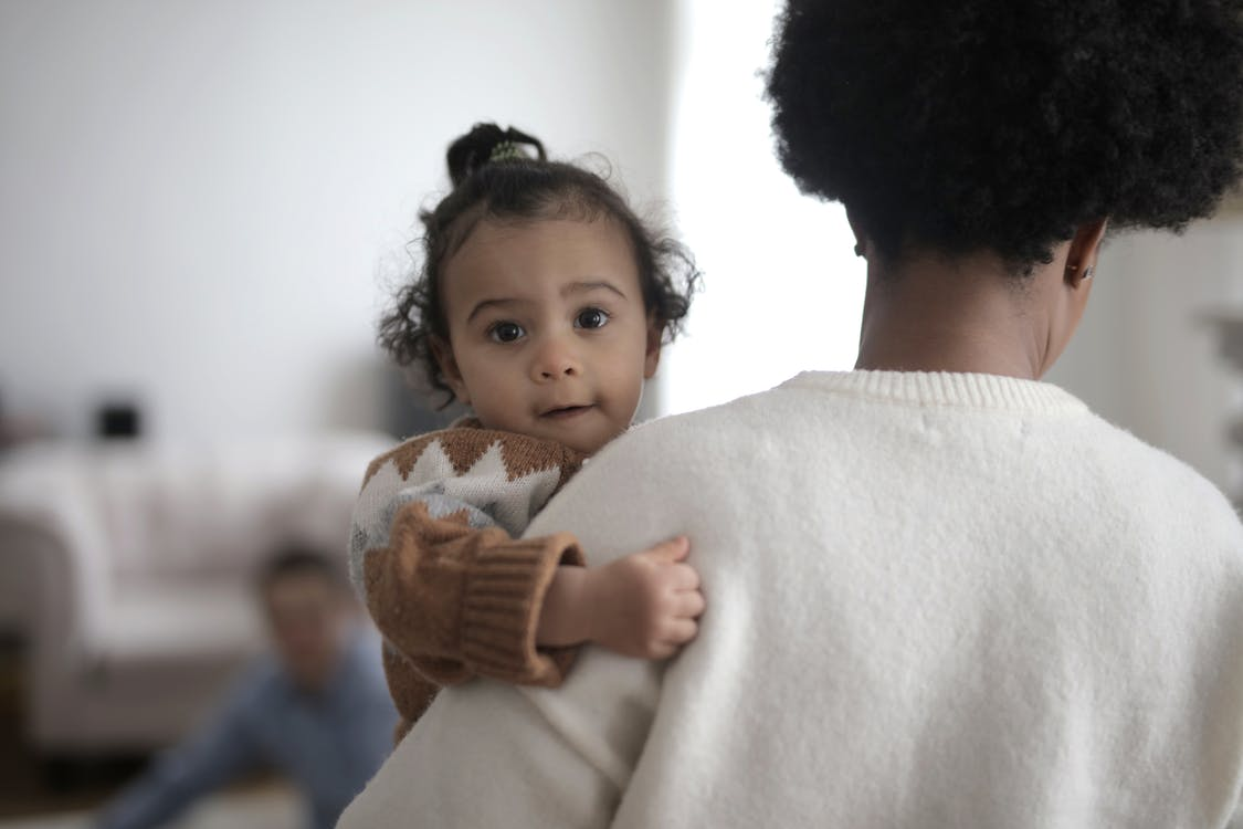Woman in White Sweater Carrying Baby in Brown Sweater